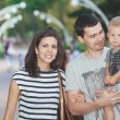 Young family with child walks in summer alley — Stock Photo #69808035