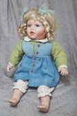 Vintage porcelain doll blonde on gray fabric background — Stockfoto