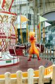 Duck toy in the seat of a colorful Merry Go Round — Stock Photo