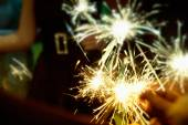 Sparkler in hands on a party — Stock Photo