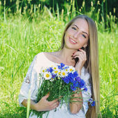 Happy woman wit bouquet of chamomiles and cornflowers — Stock Photo