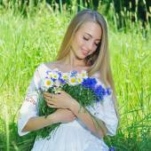 Happy woman with bouquet of chamomiles and cornflowers — Stock Photo