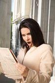 Surprised businesswoman reading journal — Stock Photo