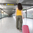 Woman pulling suitcase at airport — Stok fotoğraf #56157925