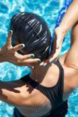 Blue polish nails swimmer placing cap — Stock Photo