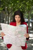 Angry woman watching a map — Stock Photo