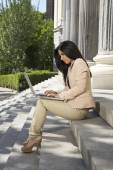 Businesswoman with laptop at staircase — Stock Photo