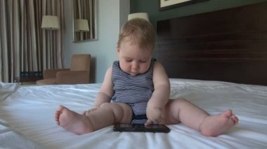 Baby with smartphone in bed — Stock Video