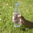 Open water plastic bottle in hand — Stock Photo #59913029
