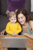 Mother and baby smiling with computer — Stock Photo