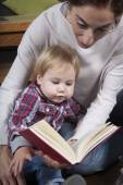Baby and mom reading — Stok fotoğraf