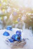 White basket with xmas balls on the snow and blue balls on christmas tree — ストック写真