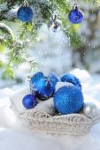 White basket with xmas balls on the snow and blue balls on christmas tree — Stock Photo