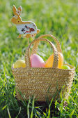 Coloured Easter eggs in a basket padded out with rabbit decorations — Stock Photo