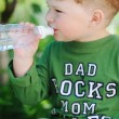 Attractive little boy drinking water from bottle outdoor — Стоковое фото #68151765