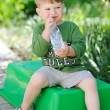 Attractive little boy drinking water from bottle outdoor — Стоковое фото #68151937