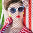 Woman wearing sunglasses lying down on a deck chair — Stock Photo #53646087