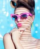 Woman wearing sunglasses under a palm tree — Stock Photo