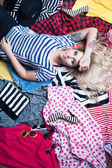 Woman lying down on a pile of clothes — Stock Photo