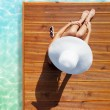 Tanning woman at the swimming pool — Stock Photo #77391382