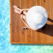 Tanning woman at the swimming pool — Stock Photo #77391494
