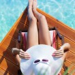 Tanning woman at the swimming pool — Stock Photo #77407652
