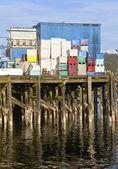 Plastic fish baskets large tank on edge of pier. — Stock Photo