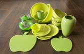 Green dishes on a dark wood floor — Stock Photo