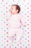 Little baby lying on blanket with colourful polka dots — Stock Photo