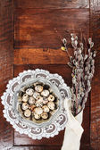 Easter composition of catkins and eggs on wooden table — Stock Photo