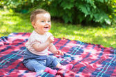 Baby sitting on a blanket in a garden — Stock Photo