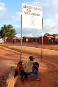 Některé děti ve znamení aids zóny u vchodu do vesnice pomerini Tanzanie Afrika — Stock fotografie