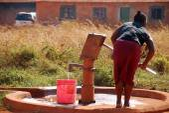 A woman and pump water from a public fountain-Pomerini-Tanzania- — Stock Photo