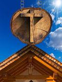 Cruz sobre el tronco del árbol con la iglesia de madera — Foto de Stock