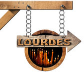 Lourdes - Wooden Sign with Votive Candles — Stock Photo