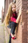 Young female teen girl pose against a brick wall. — Stock Photo