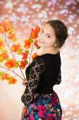 Young pretty teenage girl with autumn leaves — Stock Photo