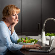 Woman using computer in kitchen — Stock Photo #53829157
