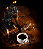 Old_coffee_mill _with_cup_of_coffee_on_tile_table — Photo