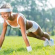 Woman in doing push ups in park — Stock Photo #52892427