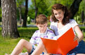 Boy and woman reading book — Stock Photo