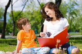 Boy and woman reading a book — Stock Photo