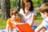 Teacher reads book to children — Stock Photo