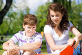 Boy and woman reading book together — Stock Photo