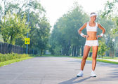 Sport kvinna som står i solig park — Stockfoto