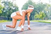 Woman runner standing in start pose — Stock Photo
