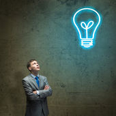 Businessman looking above at light bulb — Stock Photo