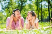Couple in summer park listening music — Stock Photo