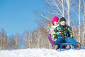 Two cute kids riding sled — Stock Photo