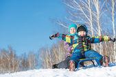 Dwa cute dzieci jazda sanki — Zdjęcie stockowe